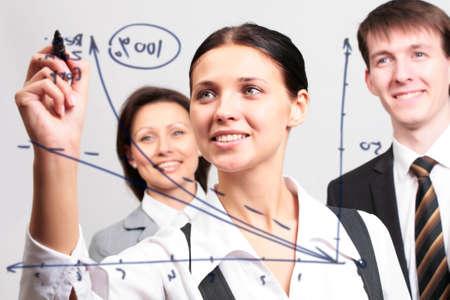 femme dessin: Femme d'affaires de dessiner un graphe sur une vitre dans un bureau
