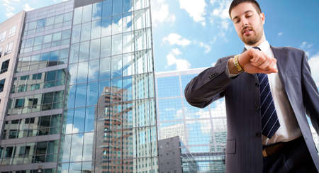 The modern businessman looking at wrist  watch on background a office building Stock Photo