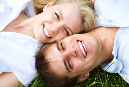 brunets: Happy couple lying on a meadow in summer Stock Photo
