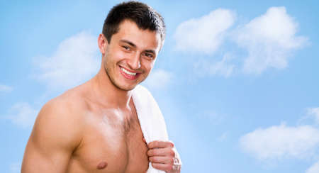 Portrait of muscular man against the blue sky photo