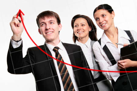 business competition: Happy businessman drawing a graph on a glass window in an office