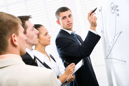 business training: Businessman presenting his ideas on whiteboard to colleagues Stock Photo