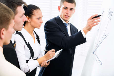 Young businessman presenting his ideas on whiteboard to colleagues