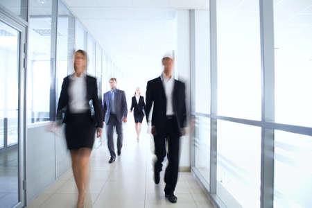personas caminando: La gente de negocios a pie en el pasillo de la oficina