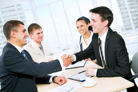 international business agreement: Business people shaking hands in office Stock Photo