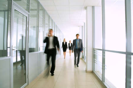 go inside: Business people walking in the office corridor