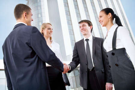 Business handshake of two successful partners at modern building photo
