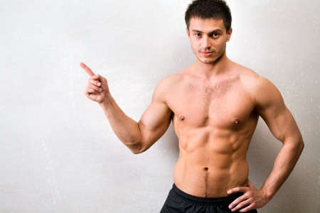 hot boy: Portrait of muscular man who is pointing a finger at a gray wall  Stock Photo