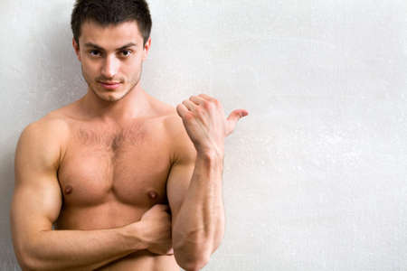 six pack: Portrait of muscular man who is pointing a finger at a gray wall  Stock Photo