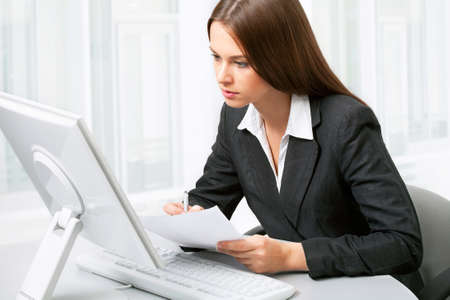 young executives: Image of pretty business woman sitting in front of computer and looking at its screen Stock Photo