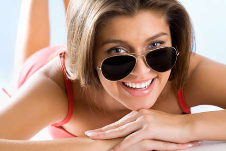 Beautiful woman with sunglasses isolated over a blue background   photo