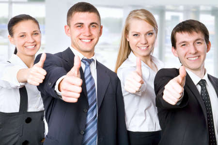 Portrait of confident young business people with thumbs up sign photo