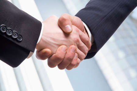 associate: Closeup picture of businesspeople shaking hands, making an agreement
