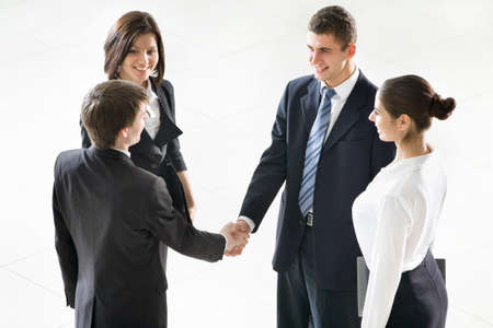 coalition: Business people shaking hands, finishing up a meeting at modern office bulding