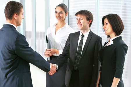 unanimous: Business people shaking hands, finishing up a meeting at office Stock Photo