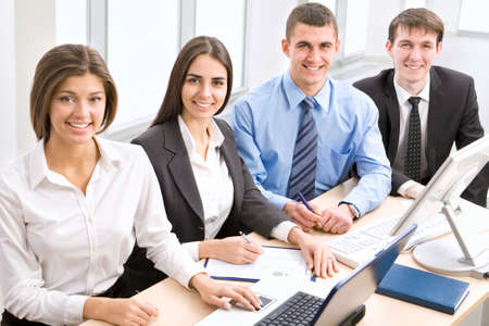 Business colleagues sitting around table and working together, looking at camera, smiling. Stock Photo - 13541732