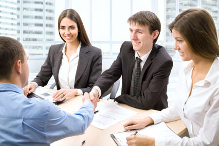 business handshake: Business people shaking hands in office Stock Photo
