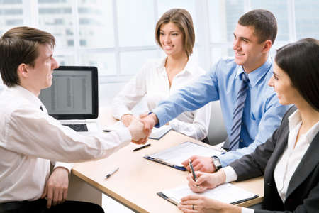 business handshake: Business people shaking hands at office