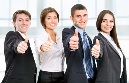 Group of happy business people giving the thumbs-up sign photo