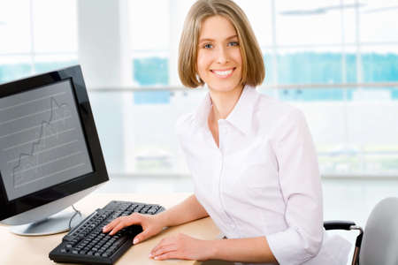 Attractive smiling young business woman using laptop at work\ desk
