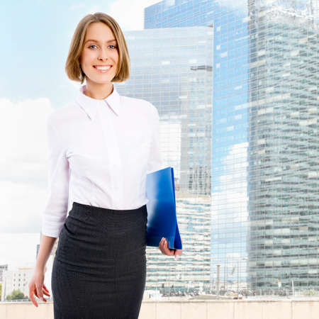 Young businesswoman against a background of modern skyscrapers photo