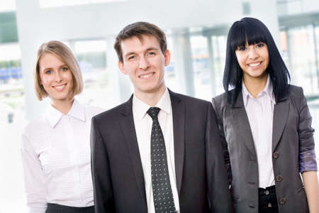 Attractive young business people standing together at office   photo
