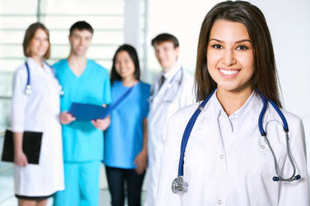 medical assistant: Portrait of young female doctor standing in frount of his team and smiling
