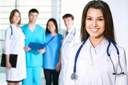 lekarz: Portret mÅ'odej kobiety lekarz stojÄ…cy w frount swojego zespoÅ'u i uÅ›miechniÄ™ta Zdjęcie Seryjne