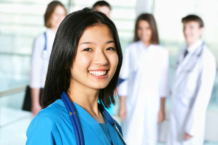 Portrait of asian female doctor standing in frount of his team and smiling  photo