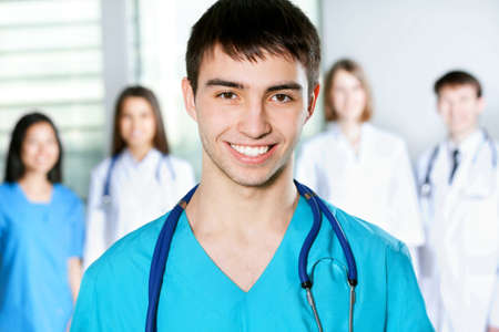 Portrait of young male doctor standing in frount of his team and smiling photo