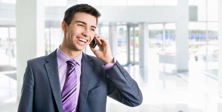Young businessman phoning in his office   photo