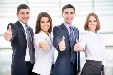 male's thumb: Portrait of happy businesspeople standing in office showing thumb up