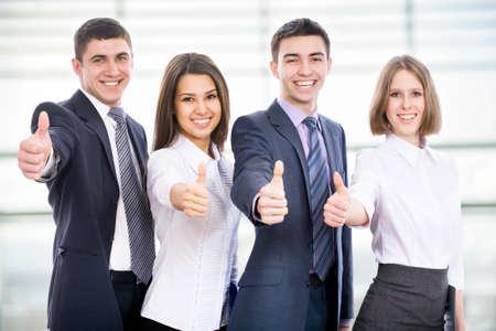 grupo de hombres: Retrato de gente de negocios feliz de pie en la oficina que muestra el pulgar hacia arriba