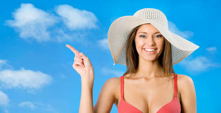 beach wear: Beautiful woman in a bikini and a hat indicates a place for your advertising