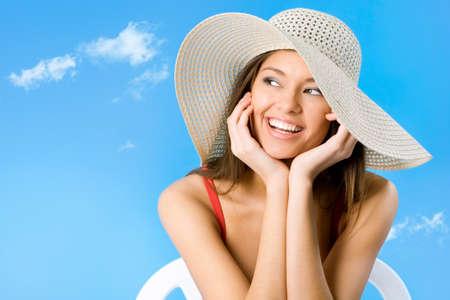 mooie vrouwen: Mooie vrouw met hoed lachend op een achtergrond van blauwe lucht Stockfoto