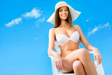 Beautiful woman in bikini relaxing on a background of blue sky photo