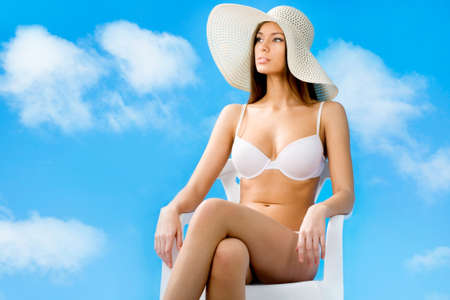 Beautiful woman in bikini relaxing on a background of blue sky Stock Photo - 14735037