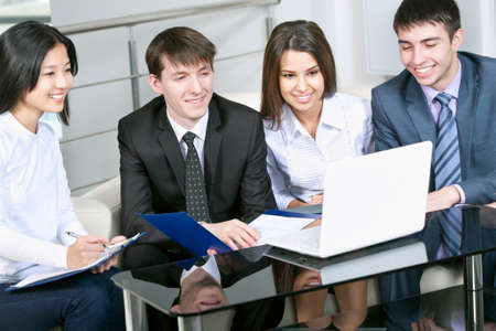 studing: Smiling business people with laptop working in board room