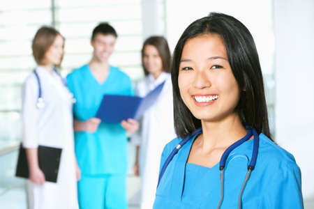 Portrait of asian female doctor standing in frount of his team and smiling