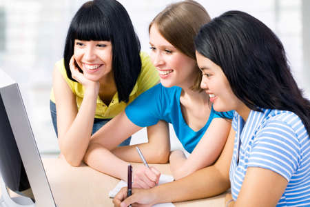 Three girl friends studying together in a classroom photo