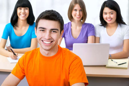 computer lessons: Happy young students studying together in a college