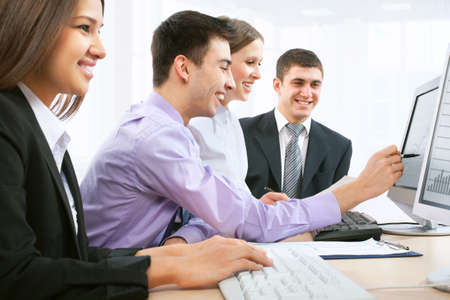 studing: Four business people during a meeting sitting around a table