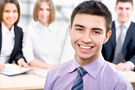 Portrait of young business man with cheerful team in background Stock Photo - 14735045