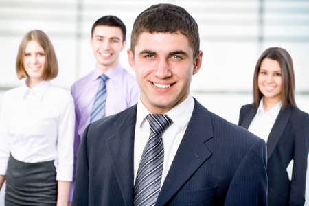 Portrait of young businessman with cheerful team in background photo