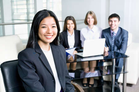competitive business: Portrait of a smiling young asian business woman in a meeting