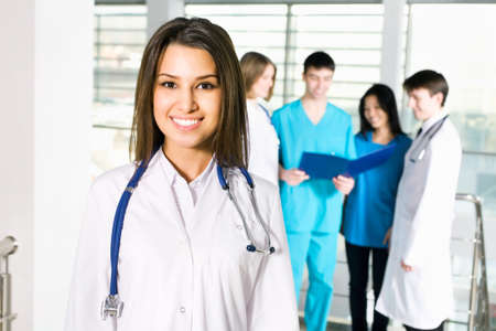 Portrait of young female doctor standing in frount of his team and smiling photo