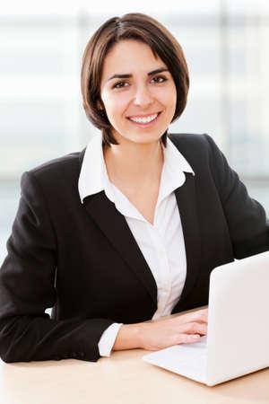 outwork: Mujer de negocios que trabajan en la computadora port�til en la oficina