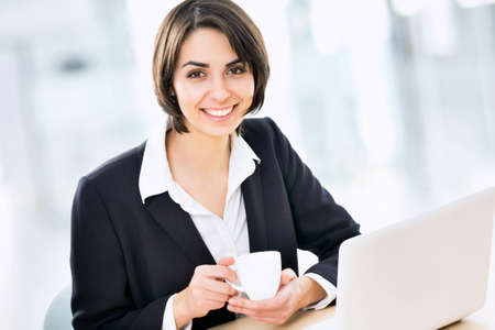 mature brunette: Portrait of happy business woman with a laptop and drinking coffee Stock Photo