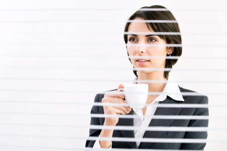 Business woman with cup of coffe looking through a venetian blind in an office photo