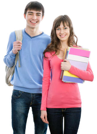 Happy young teenager students standing and smiling with books and bags
